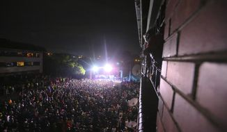 Thousands of people attend a music concert to celebrate the new year in Mbare, Harare, Friday, Jan 1, 2021. Despite a government ban on music concerts and public gatherings due to a surge in COVID-19 infections and the new and more contagious variants of the disease, thousands of people gathered in one of the country's poorest neighborhoods to celebrate the new year. (AP Photo/Tsvangirayi Mukwazhi)