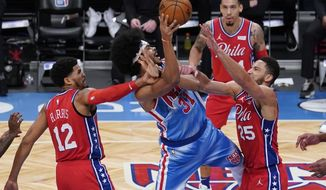 Brooklyn Nets' Jarrett Allen (31) shoots between Philadelphia 76ers' Ben Simmons (25) and Tobias Harris (12) during the second half of an NBA basketball game Thursday, Jan. 7, 2021, in New York. (AP Photo/Frank Franklin II)