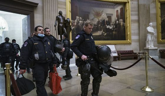 U.S. Capitol Police officers walk through the Rotunda as they and other federal police forces responded as violent protesters loyal to President Donald Trump stormed the U.S. Capitol today, at the Capitol in Washington, Wednesday, Jan. 6, 2021. (AP Photo/J. Scott Applewhite)