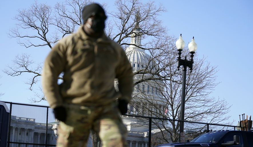 With the U.S. Capitol in the background, a member of the military walks by newly-erected fencing around the Capitol grounds the day after violent protesters loyal to President Donald Trump stormed the U.S. Congress in Washington, Thursday, Jan. 7, 2021. (AP Photo/Evan Vucci)