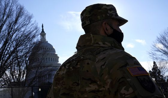 With the U.S. Capitol in the background, a member of the District of Columbia National Guard stands near newly-placed fencing around the Capitol grounds the day after violent protesters loyal to President Donald Trump stormed the U.S. Congress in Washington, Thursday, Jan. 7, 2021. (AP Photo/Matt Slocum)