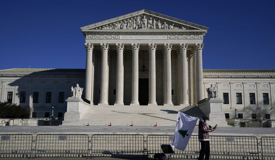 A person walks by newly-placed barricades around the Supreme Court Building, the day after violent protesters loyal to President Donald Trump stormed the U.S. Congress in Washington, Thursday, Jan. 7, 2021. (AP Photo/Evan Vucci)