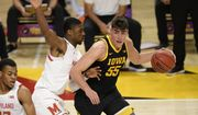 Iowa center Luka Garza (55) dribbles next to Maryland forward Jairus Hamilton, left, during the first half of an NCAA college basketball game, Thursday, Jan. 7, 2021, in College Park, Md. (AP Photo/Nick Wass)