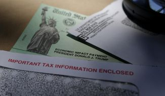 In this April 23, 2020, photo, President Donald Trump's name is seen on a stimulus check issued by the IRS to help combat the adverse economic effects of the COVID-19 outbreak, in San Antonio. The U.S. Treasury and IRS have sent out the bulk of the second economic impact payments, which are intended to provide some relief to Americans. However, frustration is high among millions of people who did not receive payments yet and must wait for the mail or file their taxes before they receive it. (AP Photo/Eric Gay) **FILE**