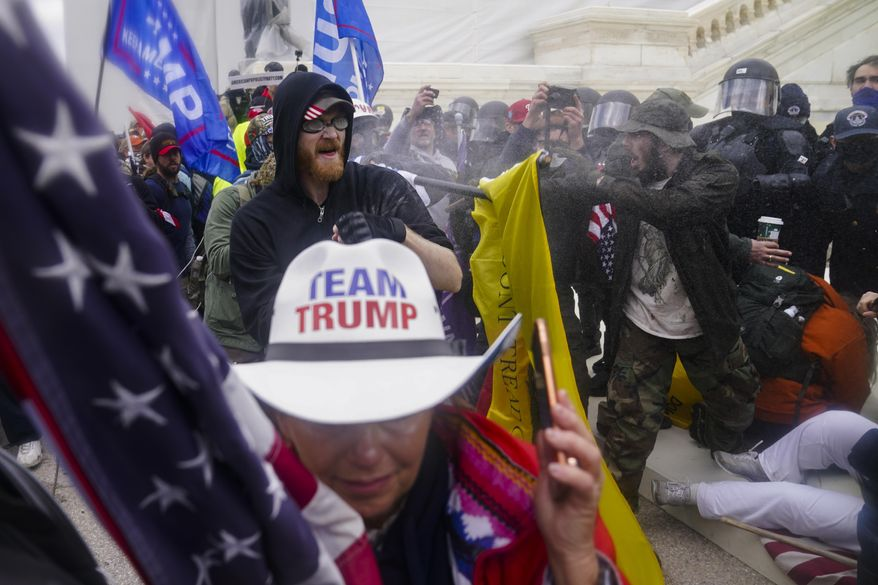 Trump supporters try to break through a police barrier, Wednesday, Jan. 6, 2021, at the Capitol in Washington. As Congress prepared to affirm President-elect Joe Biden's victory, thousands of people gathered to show their support for President Donald Trump and his claims of election fraud.(AP Photo/John Minchillo)