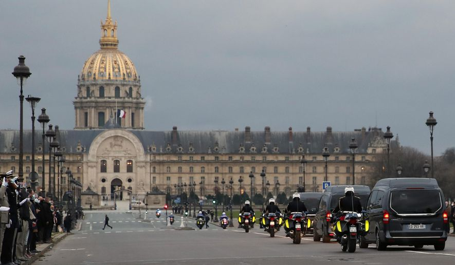 The hearse convoy of late French forces soldiers , who were killed in Mali when an improvised explosive device hit their armored vehicle last week, rides on his way to the Invalides for a national tribute, in Paris, Monday, Jan. 4, 2021. The soldiers were participating in a military operation in the Hombori area of Mali's central Mopti province, part of a larger mission aiming at fighting Islamist extremists in Africa's Sahel region, as part of Operation Barkhane. (AP Photo/Francois Mori)