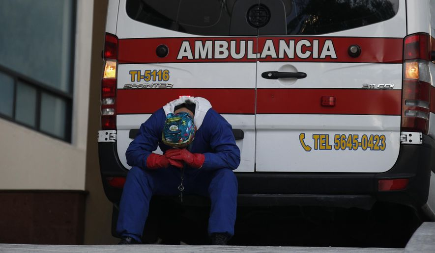A paramedic rests behind his ambulance, as ambulance staff wait hours for the COVID-19 patients they are transporting to be admitted, at Siglo XXI Medical Center in Mexico City, Thursday, Jan. 7, 2021. A line of five ambulances spent hours outside the hospital Thursday afternoon waiting for their patients to be admitted, as hospitals in the capital near full capacity amid an unprecedented surge in coronavirus cases in Mexico.(AP Photo/Rebecca Blackwell)