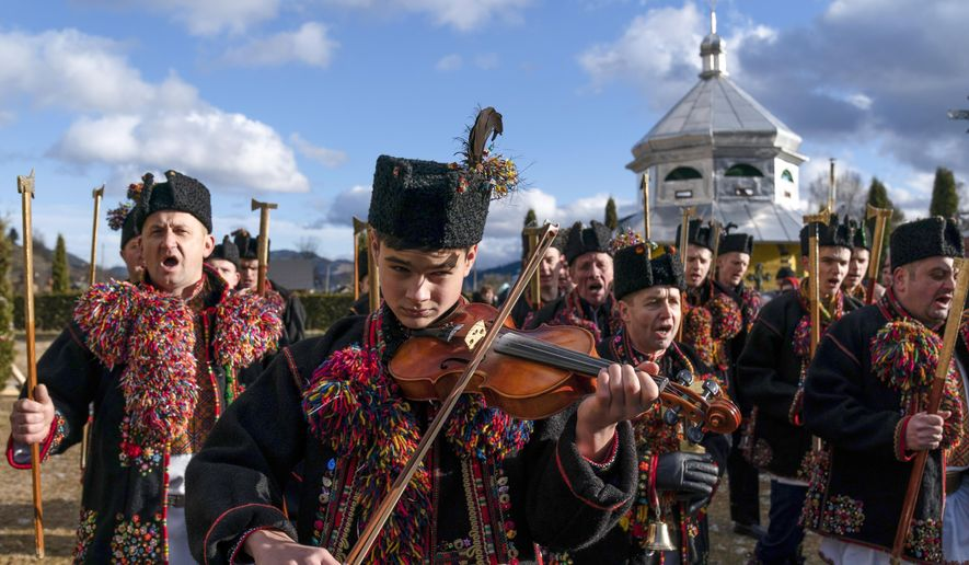 An ethnic Hutsul man, an ethnic group spanning parts of western Ukraine, plays a violin as others, all wearing traditional colorful clothes, sing a kolyada song during the Orthodox Christmas celebration near the Holy Trinity church in Iltsi village, Ivano-Frankivsk region of Western Ukraine, Thursday, Jan. 7, 2021. Orthodox Christians celebrate Christmas on Jan. 7, in accordance with the Julian calendar. (AP Photo/Evgeniy Maloletka)