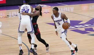 Chicago Bulls guard Coby White, center, runs into Sacramento Kings forward Richaun Holmes, left, as he tries to guard Kings guard De'Aaron Fox during the first quarter of an NBA basketball game in Sacramento, Calif., Wednesday, Jan. 6, 2021. (AP Photo/Rich Pedroncelli)