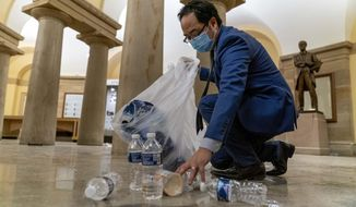 Rep. Andy Kim, D-N.J., cleans up debris and trash strewn across the floor in the early morning hours of Thursday, Jan. 7, 2021, after protesters stormed the Capitol in Washington, on Wednesday. (AP Photo/Andrew Harnik)