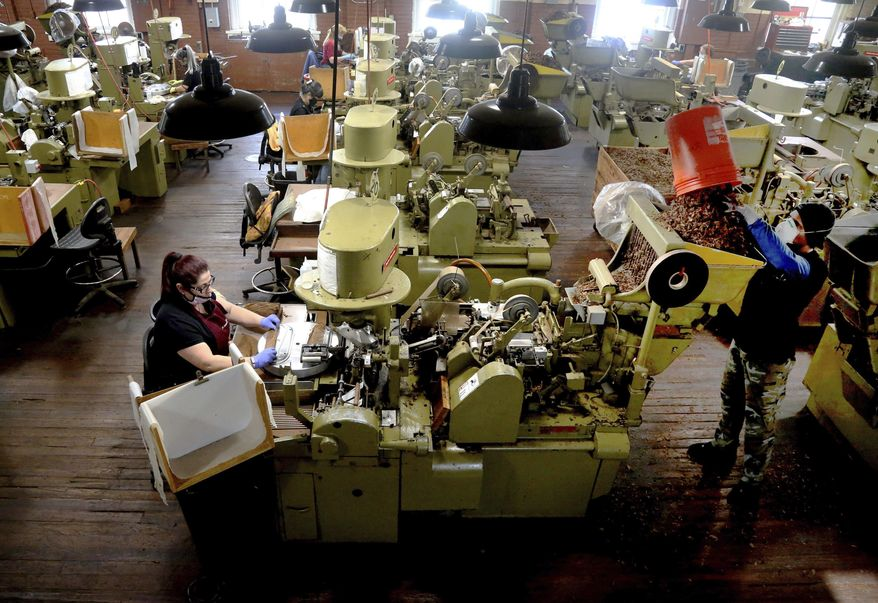 In this Dec. 14, 2020, file photo, Zeida Hernandez, of Tampa, Fla., left, makes Factory Throwout cigars using an antique hand-operated cigar machine at the J.C. Newman Cigar Co., Tampa's last cigar factory, in Fla. American factories grew in December at the fastest pace in more than two years as manufacturing continued to weather the pandemic better than the battered services sector. (Douglas R. Clifford/Tampa Bay Times via AP)