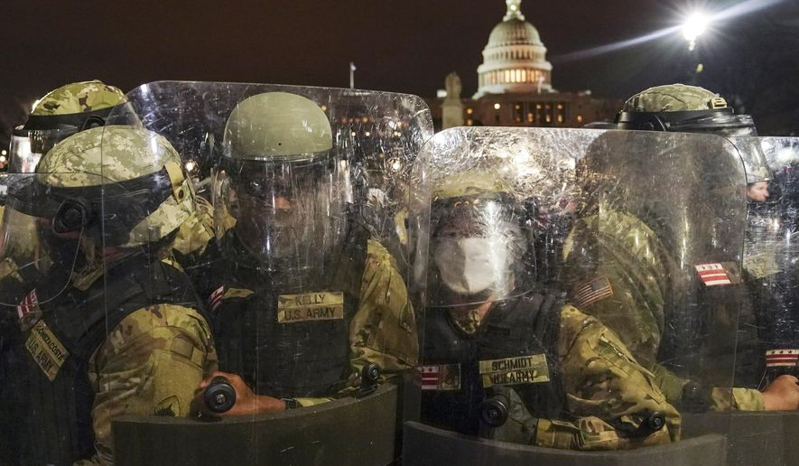DC National Guard stand outside the Capitol, Wednesday night, Jan. 6, 2021, after a day of rioting protesters. It's been a stunning day as a number of lawmakers and then the mob of protesters tried to overturn America's presidential election, undercut the nation's democracy and keep Democrat Joe Biden from replacing Trump in the White House. (AP Photo/John Minchillo)