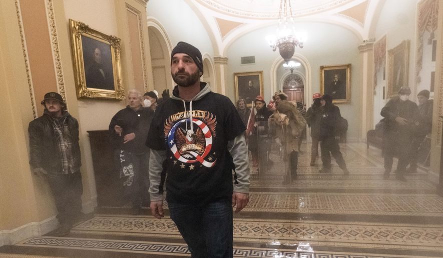 Smoke fills the walkway outside the Senate Chamber as supporters of President Donald Trump are confronted by U.S. Capitol Police officers inside the Capitol, Wednesday, Jan. 6, 2021 in Washington. (AP Photo/Manuel Balce Ceneta)