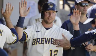 FILE - In this March 1, 2020, file photo, Milwaukee Brewers' Justin Smoak is congratulated after scoring during a spring training baseball game against the Cincinnati Reds in Phoenix. The Yomiuri Giants of Japanese baseball on Thursday, Jan. 7, 2021, announced they have agreed to a deal with Smoak. Smoak played last season with the Milwaukee Brewers and the San Francisco Giants.. (AP Photo/Darron Cummings, File)