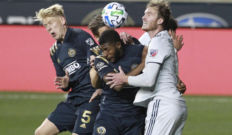 Philadelphia Union Jakob Glesnes, left, and Mark McKenzie battle for the ball against New England Revolutions Henry Kessler during the second half of an MLS soccer playoff match Tuesday, Nov. 24, 2020, in Chester, Pa. (Charles Fox/The Philadelphia Inquirer via AP)