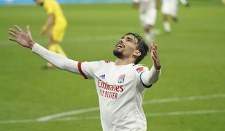 FILE - In this Wednesday, Dec. 23, 2020 file photo, Lyon's Lucas Paqueta celebrates after scoring his sides's third goal during the French League One soccer match between Lyon and Nantes, in Decines, near Lyon, central France. When the best player in Lyon's history phoned AC Milan's greatest defender they talked business. Juninho persuaded Paolo Maldini, Milan's technical director and his former Champions League adversary to sell midfielder Lucas Paqueta to Lyon for 20 million euros ($24.5 million). It has proved the signing of the French season, with Paqueta the driving force in a Lyon side three points clear at the top and heading into Saturday's trip to Rennes unbeaten in 15 games. (AP Photo/Laurent Cipriani, File)