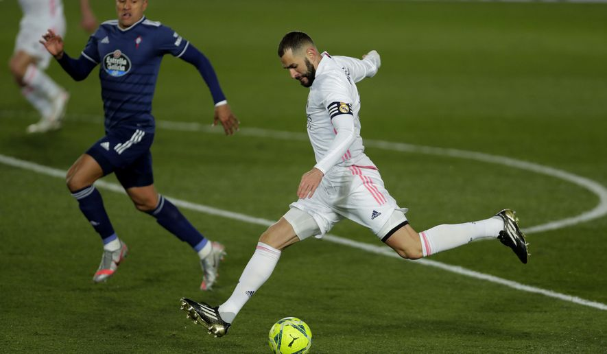 Real Madrid's Karim Benzema shoots the ball during the Spanish La Liga soccer match between Real Madrid and Celta Vigo at the Alfredo Di Stefano stadium in Madrid, Spain, Saturday, Jan. 2, 2021. (AP Photo/Manu Fernandez)