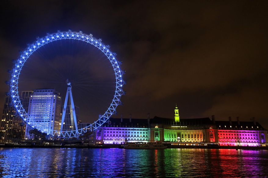 The London Eye on the bank of the River Thames is lit with blue lights to show support for the NHS in London, Thursday, Jan. 7, 2021. Buildings across the country are being lit with blue lights to thank the work by NHS staff in caring for people during the COVID-19 pandemic. (AP Photo/Kirsty Wigglesworth)