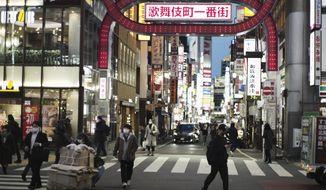 People wearing face masks to help curb the spread of the coronavirus walk across an intersection at Shinjuku neighborhood of Tokyo on Thursday, Jan. 7, 2021. (AP Photo/Hiro Komae)