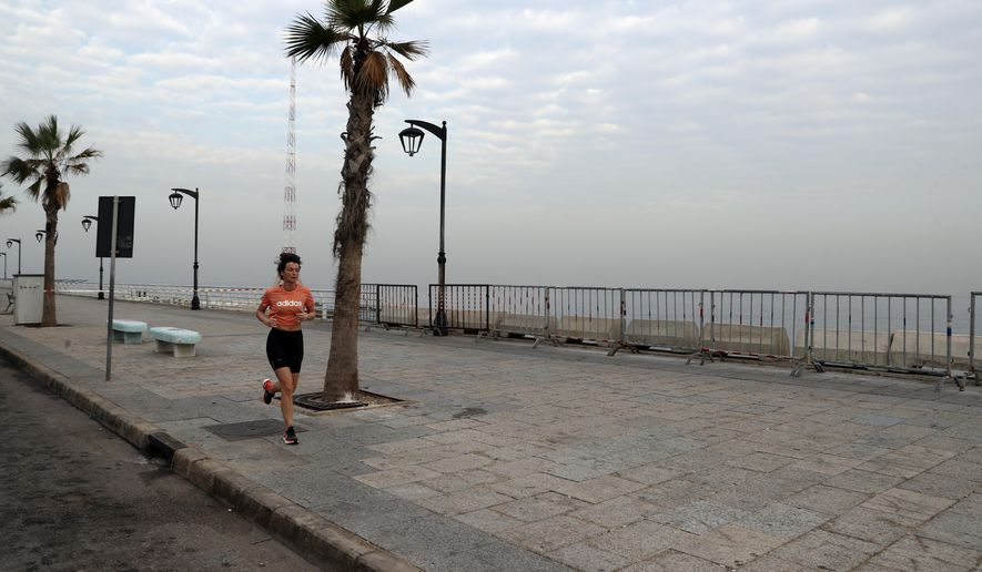 A woman runs on the empty waterfront promenade as the country begins a three-week lockdown to limit the spread of coronavirus amid a post-holiday surge in the past 10 days in Beirut, Lebanon, Thursday, Jan. 7, 2021. (AP Photo/Bilal Hussein)