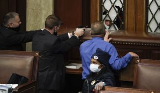 Security forces draw their guns as protesters try to break into the House Chamber at the U.S. Capitol on Wednesday, Jan. 6, 2021, in Washington. (AP Photo/J. Scott Applewhite)