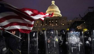 Police stand guard after a day of riots at the U.S. Capitol in Washington on Wednesday, Jan. 6, 2021. (AP Photo/Julio Cortez)