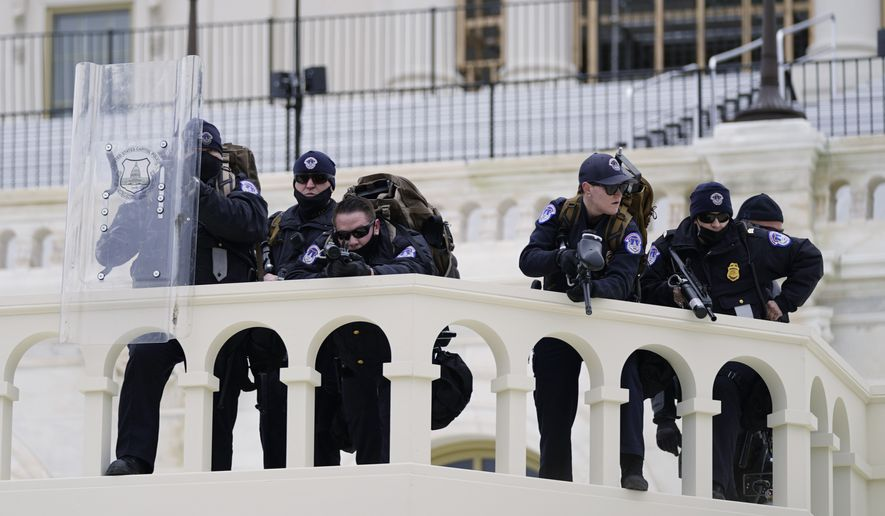 Police keep a watch on demonstrators who tried to break through a police barrier, Wednesday, Jan. 6, 2021, at the Capitol in Washington. As Congress prepared to affirm President-elect Joe Biden's victory, thousands of people gathered to show their support for President Donald Trump and his claims of election fraud. (AP Photo/Julio Cortez) ** FILE **