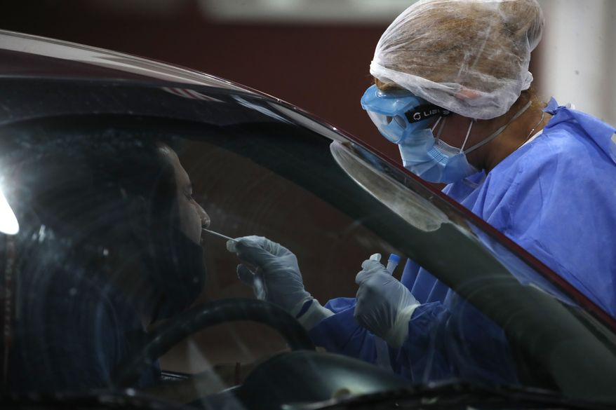 In this file photo, a healthcare worker takes a nasal swab sample to test for COVID-19, in Buenos Aires, Argentina, Friday, Jan. 8, 2021. (AP Photo/Natacha Pisarenko)  **FILE**