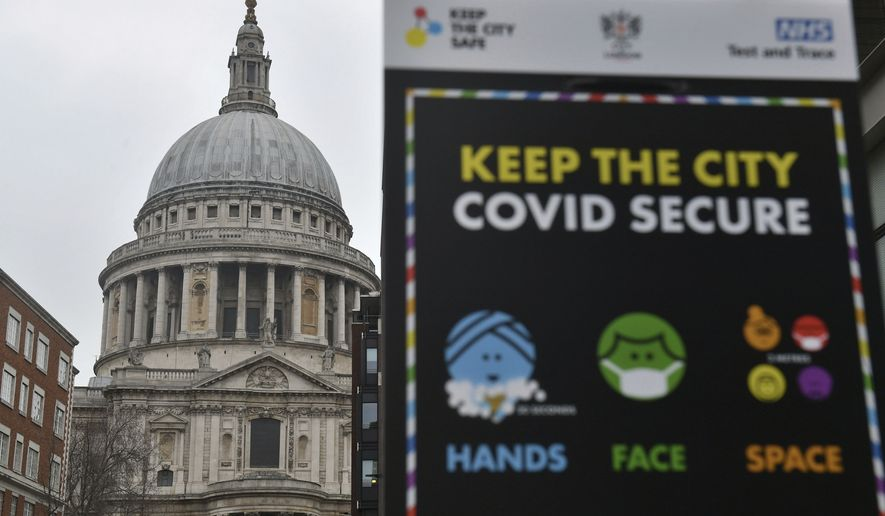 """Covid-19 signage in front of St Paul's Cathedral, after Mayor of London Sadiq Khan declared a """"major incident"""" as the spread of coronavirus threatens to """"overwhelm"""" the capital's hospitals during England's third national lockdown to curb the spread of coronavirus, in London, Friday, Jan. 8, 2021. (Dominic Lipinski/PA via AP)"""