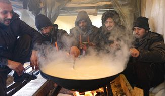Migrants cook inside a makeshift shelter at the Lipa camp, outside Bihac, Bosnia, Friday, Jan. 8, 2021. A fresh spate of snowy and very cold winter weather on has brought more misery for hundreds of migrants who have been stuck for days in a burnt out camp in northwest Bosnia waiting for heating and other facilities. (AP Photo/Kemal Softic)