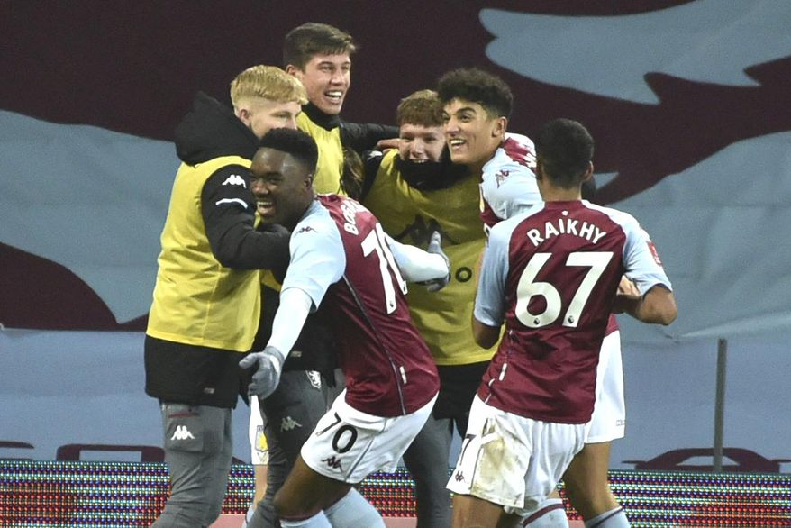 Aston Villa's players celebrate a goal by Aston Villa's Louie Barry during the FA Cup 3rd round soccer match between Aston Villa and Liverpool at Villa Park stadium in Birmingham, England, Friday, Jan. 8, 2021. (AP Photo/Rui Vieira)