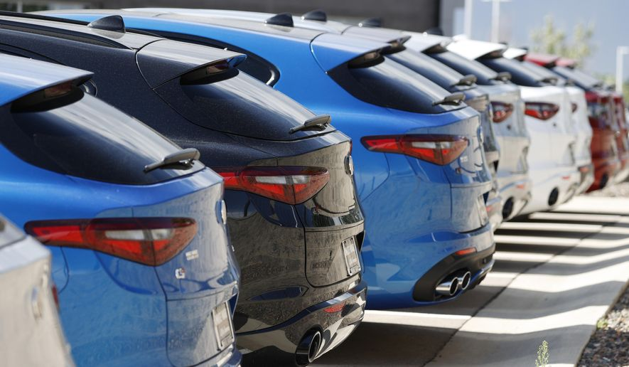 FILE - In this July 19, 2020, file photo, a long row of unsold 2020 Stelvio sports-utility vehicles sits at an Alfa Romeo dealership, in Highlands Ranch, Colo. U.S. consumer borrowing rose 4.4% in November 2020, its strongest showing in five months, led by strong gains in auto and student loans that offset a drop in credit card borrowing. The Federal Reserve said Friday, Jan. 8, 2021, that the rise represented an increase of $15.3 billion, the best showing since June. (AP Photo/David Zalubowski, File)