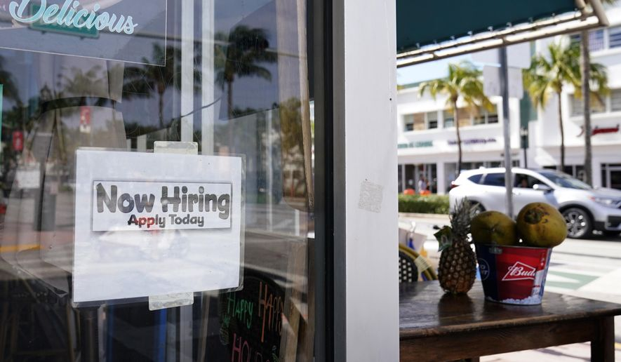 """A """"Now Hiring,"""" sign is shown in the window of a restaurant, Thursday, Jan. 7, 2021, in Miami Beach, Fla. America's employers likely cut back on hiring last month, and may have even shed jobs, as the economy suffers from a resurgent virus that has caused many consumers to cut back on spending and states and cities to reimpose business restrictions. (AP Photo/Wilfredo Lee)"""