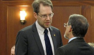 FILE - In this March 5, 2020, file photo, Alaska Republican House Minority Leader Lance Pruitt, left, speaks with Rep. George Rauscher on the floor of the House in Juneau, Alaska. The Alaska Supreme Court is set to hear arguments Friday, Jan. 8, 2021, in an election challenge brought by Pruitt. A recount found Pruitt lost his Anchorage seat to Democrat Liz Snyder by 11 votes. Pruitt's attorney says the court should order a new election, arguing that election officials did not do enough to notify voters of a polling place change. (AP Photo/Becky Bohrer, File)