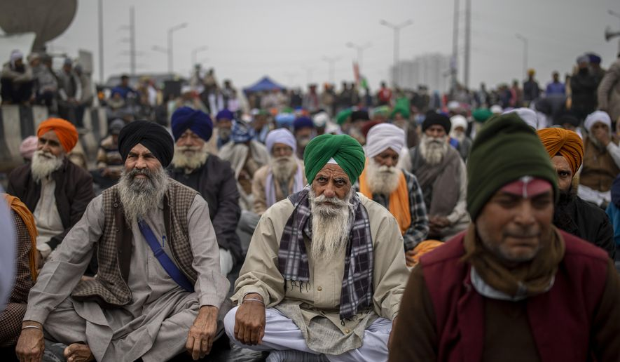 Farmers listen to a speaker as they block a major highway in protest against new farm laws, at the Delhi-Uttar Pradesh state border, India, Friday, Jan. 8, 2021. (AP Photo/Altaf Qadri)