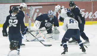 Winnipeg Jets goaltender Eric Comrie (1) saves the shot during their NHL hockey training camp practice in Winnipeg, Manitoba, Wednesday, Jan. 6, 2021. (John Woods/The Canadian Press via AP)