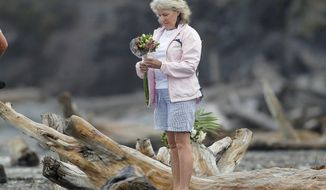 A woman prepares to lay flowers on a beach following a shark attack at Bowentown near Waihi in New Zealand, Friday, Jan 8, 2021. A woman has died Thursday, Jan. 7, in what appears to be New Zealand's first fatal shark attack in eight years, police say. (George Novak/Bay of Plenty Times via AP)