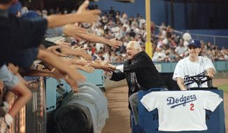 FILE - Former Los Angeles Dodgers manager Tommy Lasorda laughs as he reaches out for fans' hands on as he is driven around Dodger Stadium in Los Angeles for a farewell lap following a ceremony in his honor, in this Friday, Sept. 7, 1996, file photo. Lasorda, who guided the Los Angeles Dodgers to two World Series titles and later became an ambassador for the sport he loved during his 71 years with the franchise, has died. He was 93. The Dodgers said Friday, Jan. 8, 2021, that he had a heart attack at his home in Fullerton, California. Resuscitation attempts were made on the way to a hospital, where he was pronounced dead shortly before 11 p.m. Thursday. (AP Photo/Susan Sterner, File)