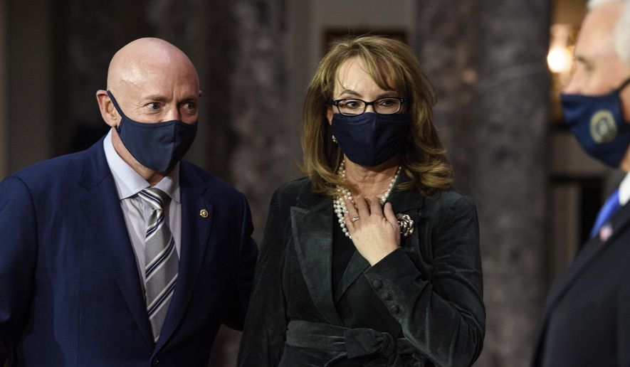Sen. Mark Kelly, D-Ariz., talks with his wife former Rep. Gabby Giffords, D-Ariz., and Vice President Mike Pence after participating in a re-enactment of his swearing-in Wednesday, Dec. 2, 2020, on Capitol Hill in Washington. (Nicholas Kamm/Pool via AP)
