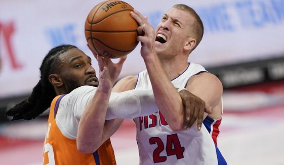 Detroit Pistons center Mason Plumlee (24) is fouled by Phoenix Suns forward Jae Crowder during the second half of an NBA basketball game, Friday, Jan. 8, 2021, in Detroit. (AP Photo/Carlos Osorio)