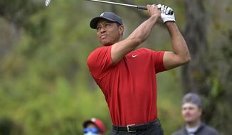 """FILE - Tiger Woods watches his tee shot on the fourth hole during the final round of the PNC Championship golf tournament in Orlando, Fla., on Dec. 20, 2020. """"Tiger,"""" a two part documentary about Woods premieres Jan. 10 on HBO. (AP Photo/Phelan M. Ebenhack, File)"""
