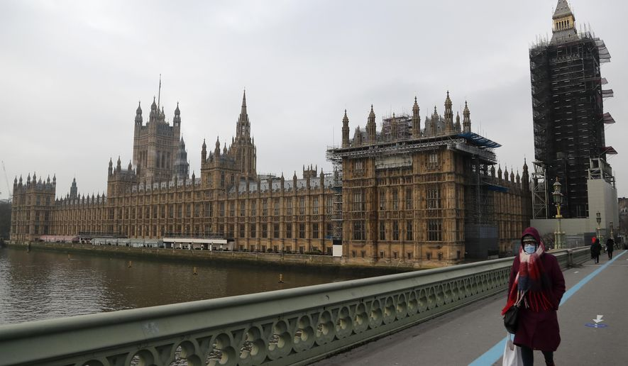 A woman wearing a face mask, walks across Westminster Bridge past the Houses of Parliament in London, Friday, Jan. 8, 2021. Britain's Prime Minister Boris Johnson has ordered a new national lockdown for England which means people will only be able to leave their homes for limited reasons, with measures expected to stay in place until mid-February. (AP Photo/Frank Augstein)