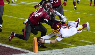 Washington Football Team quarterback Taylor Heinicke (4) dives to score a touchdown against Tampa Bay Buccaneers inside linebackers Kevin Minter (51) and Lavonte David (54) during the second half of an NFL wild-card playoff football game, Saturday, Jan. 9, 2021, in Landover, Md. (AP Photo/Julio Cortez)