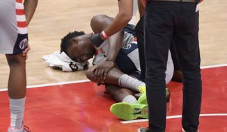 Washington Wizards center Thomas Bryant (13) lies injured on the court during the first half of an NBA basketball game against the Miami Heat, Saturday, Jan. 9, 2021, in Washington. (AP Photo/Nick Wass)  **FILE**