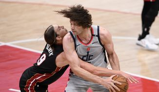 Miami Heat forward Kelly Olynyk (9) battles for the ball against Washington Wizards center Robin Lopez, right, during the first half of an NBA basketball game, Saturday, Jan. 9, 2021, in Washington. (AP Photo/Nick Wass) **FILE**