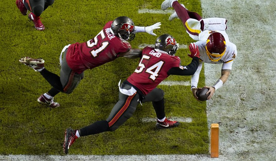 Washington Football Team quarterback Taylor Heinicke (4) dives towards the end zone to score a touchdown against Tampa Bay Buccaneers inside linebackers Kevin Minter (51) and Lavonte David (54) during the second half of an NFL wild-card playoff football game, Saturday, Jan. 9, 2021, in Landover, Md. (AP Photo/Al Drago)