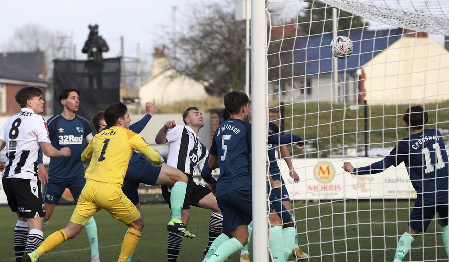 Chorley's Connor Hall, black and white strip at centre, scores his side's first goal of the game against Derby County, during the English FA Cup third round match at Victory Park in Chorley, England, Saturday Jan. 9, 2021. (Martin Rickett/PA via AP)