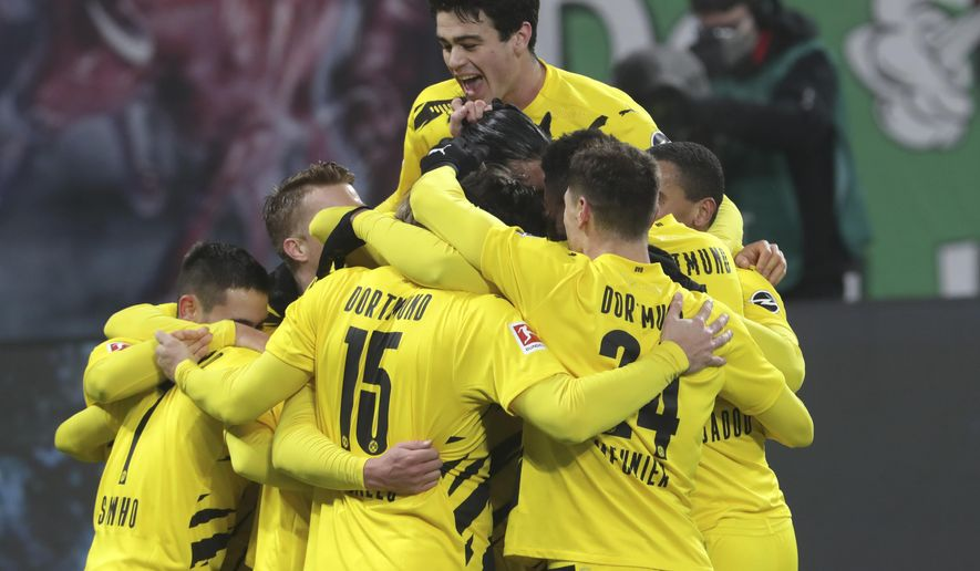Dortmund players celebrate after Dortmund's Erling Haaland scored his side's second goal during the German Bundesliga soccer match between RB Leipzig and Borussia Dortmund in Leipzig, Germany, Saturday, Jan. 9, 2021. (AP Photo/Michael Sohn)