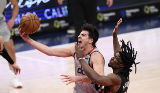 Washington Wizards forward Deni Avdija, left, goes to the basket past Miami Heat forward Precious Achiuwa (5) during the first half of an NBA basketball game, Saturday, Jan. 9, 2021, in Washington. Achiuwa was called for a foul on the play. (AP Photo/Nick Wass)