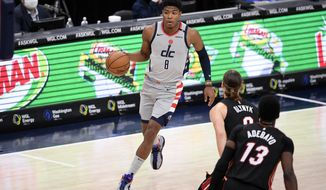 Washington Wizards forward Rui Hachimura (8), of Japan, dribbles the ball during the first half of an NBA basketball game against the Miami Heat forward Kelly Olynyk (9) and center Bam Adebayo (13), Saturday, Jan. 9, 2021, in Washington. (AP Photo/Nick Wass)